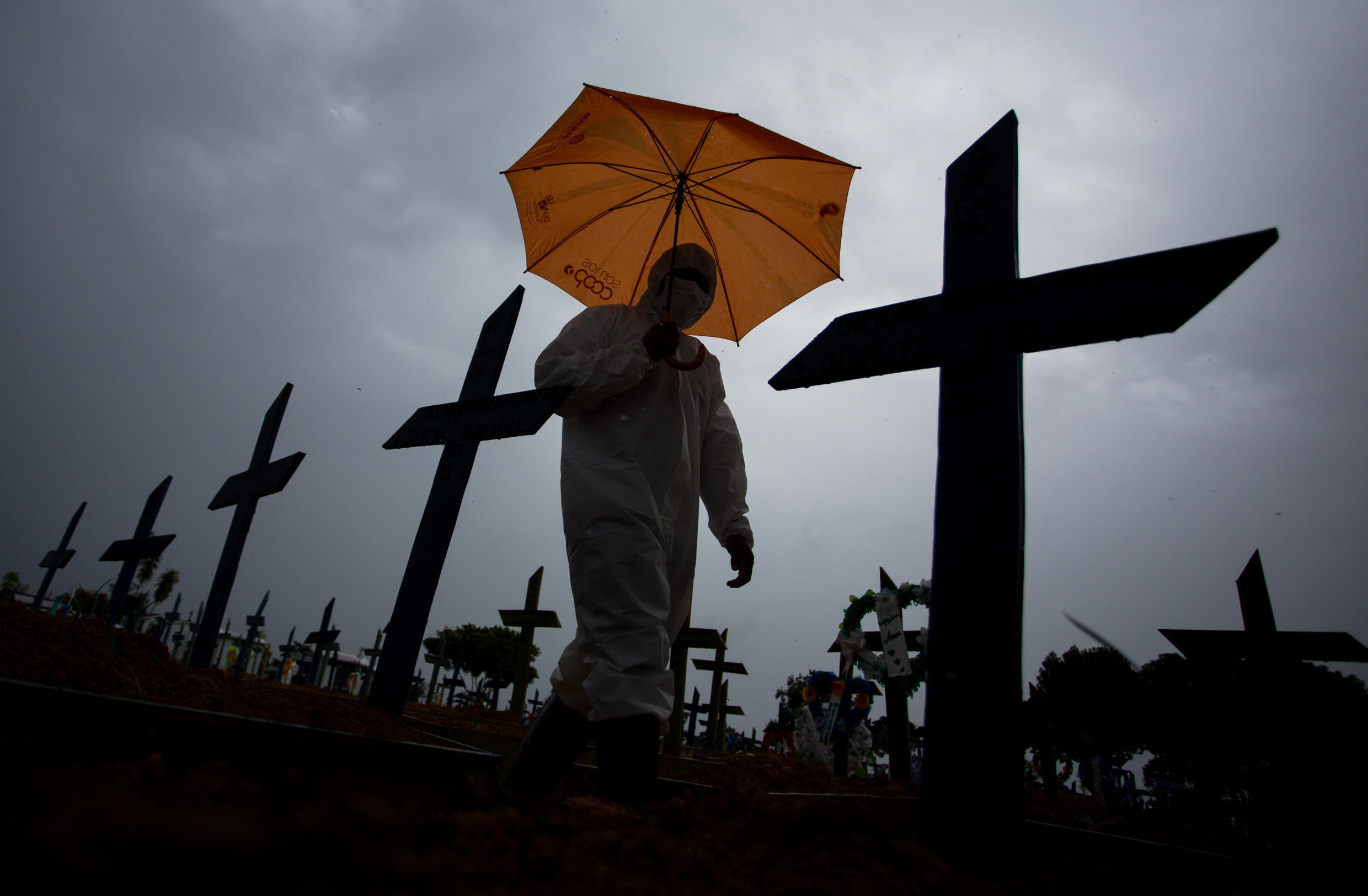 Image d'archive RFI : A workers wearing a protective suit and carrying an umbrella walks past the graves of COVID-19 victims in Manaus, Brazil