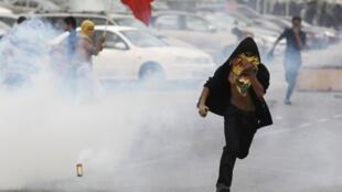 Manifestante do Partido al Wefaq corre de bomba de gás atirada pela polícia na zona oeste da capital Manama