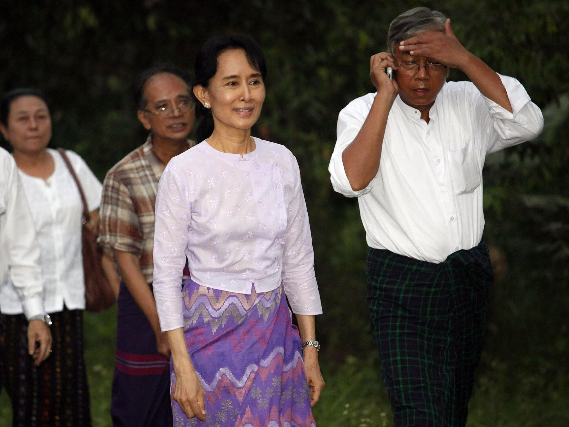 Aung San Suu Kyi leaves her house with members of her National League for Democracy