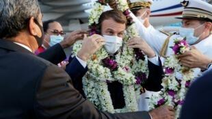 El presidente de Francia, Emmanuel Macron (centro), es envuelto en guirnaldas mientras es recibido en la pista a su llegada al aeropuerto internacional de Faa'a para una visita a Tahití, en la Polinesia francesa, el 24 de julio de 2021
