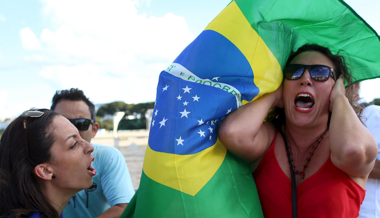 A gauche, une manifestante hostile au gouvernement semble délivrer des messages insoutenables à cette femme à droite, un soutien de l'équipe au pouvoir. Brasilia, 16 mars 2016.