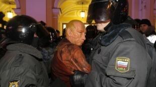 Des policiers russes ceinturent un manifestant arborant un masque à l'effigie de Vladimir Poutine à Saint-Pétersbourg, le 8 décembre 2011.