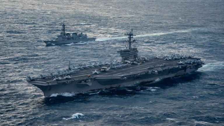 This US Navy handout photo obtained March 15, 2017 shows the aircraft carrier USS Carl Vinson (CVN 70), foreground,as it transits the East China Sea with the Japan Maritime Self-Defense Force Murasame-class destroyer JS Samidare (DD 106) on March 9, 2017.