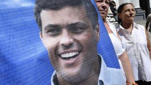 Manifestantes exhiben un afiche representando a Leopoldo López.