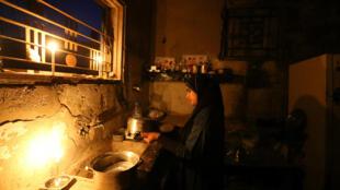 Menina palestina limpa cozinha de sua casa durante corte de luz na Faixa de Gaza.