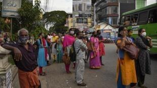 Watu wakivaa barakoa wakijilinda dhidi ya maambukizi ya corona kwenye kituo cha mabasi huko Kochi, katika Jimbo la Kerala, India.
