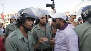 Un manifestant prend à parti verbalement des policiers lors d'une manifestation contre le projet de réforme constitutionnelle présenté par le roi Mohamed VI..