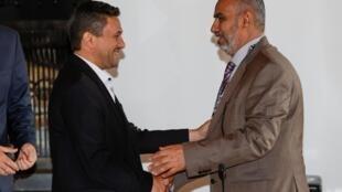 Abdulkader al-Murtada, chef du comité d'échange de prisonniers houthis, serre la main de Hadi Haig, chef de la délégation du gouvernement yéménite, après la mise en œuvre de l'accord, en Suisse, le 27 septembre 2020.