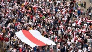 Les manifestants brandissant un immense drapeau aux couleurs de l'opposition à Minsk, le 23 août 2020.