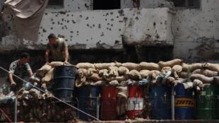 Au Liban, des soldats de l'armée nationale démontent une barricade après des combats à Tripoli, le 9 juin 2013. Cette ville du nord est devenue le creuset principal des tensions régionales.