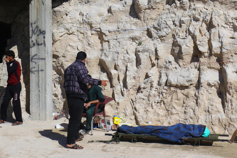 Un homme se tient près du corps d'une victime de l'attaque aérienne sur Khan Chaykhoun, dans le nord-ouest de la Syrie, le 4 avril 2017.