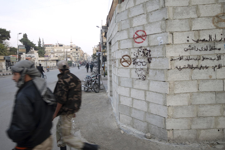 Membros do Exército Sírio LIvre (oposição) caminha em Duma, nos arredores da capital Damasco.