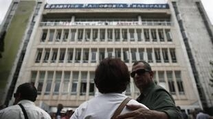 Manisfestantes junto à sede da televisão grega