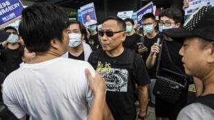 Un manifestant pro-police (g) est retenu par un policier alors qu'il crie des insultes à un manifestant anti-gouvernement (c) à Hong Kong, ce 30 juin 2019.