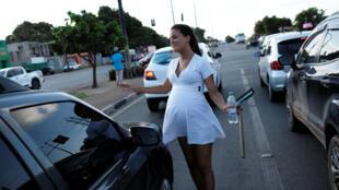 Một phụ nữ trẻ Venezuela làm công việc lau kính xe cho khách qua đường để kiếm thêm thu nhập. Ảnh chụp ngày 24/08/2018 tại Boa Vista, Romaia.