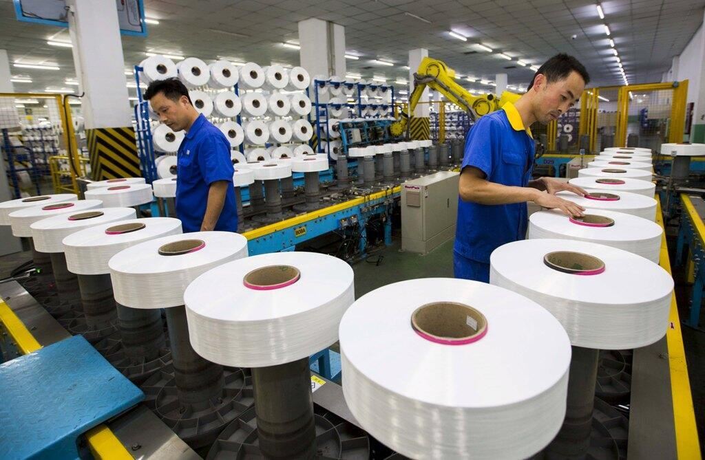 Employees work along a production line of a textile factory in Suzhou, Jiangsu province, China, June 13, 2015. China's factory sector contracted by the most in 15 months in July as shrinking orders depressed output, a preliminary private survey showed on J