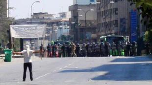 Manifestante desafia tropa de choque do governo sírio, nas proximidades de Homs.