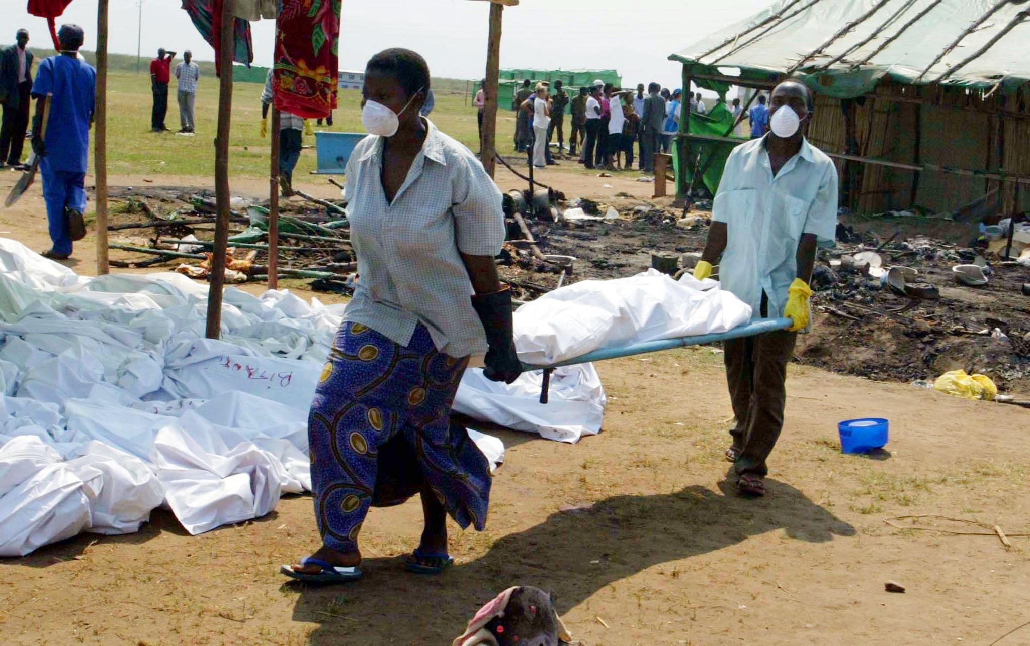 Des volontaires transportent les corps des 160 victimes, le 14 août 2004, au lendemain du massacre du camp de réfugiés de Gatumba.