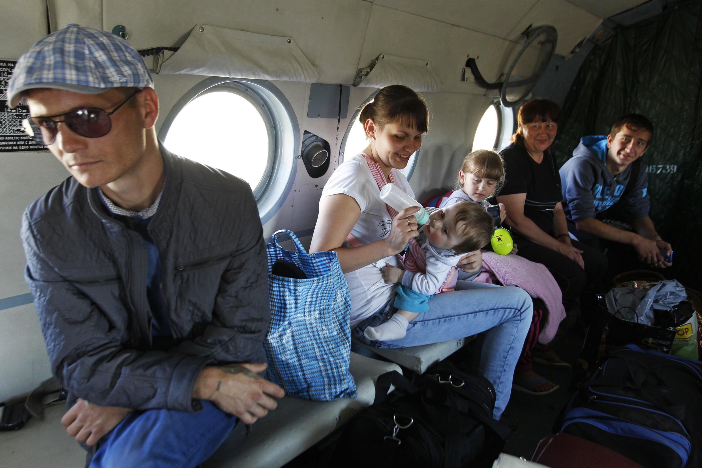 Famílias ucranianas que fogem dos combates em Donetsk são transferidas de helicóptero para campo de refugiados instalado em Rostov, na fronteira russo-ucraniana.