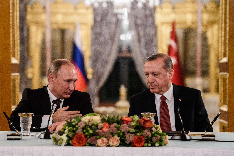 O presidente russo Vladimir Putin (esq) fala com o presidente turco Recep Tayyip Erdogan (dir) a 10 de Outubro de 201 em Istanbul.