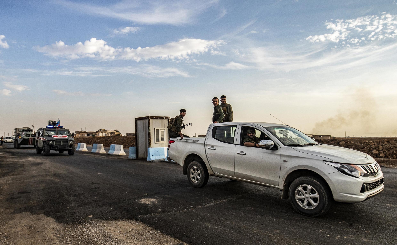 Des membres des forces de sécurité kurdes syriennes à l'arrière d'une camionnette pendant une patrouille conjointe, le 24 octobre 2019.