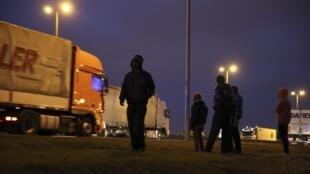 Des migrants attendent sur le bord de la route à Calais, près du terminal du ferry, dans l'espoir de passer en Grande-Bretagne.