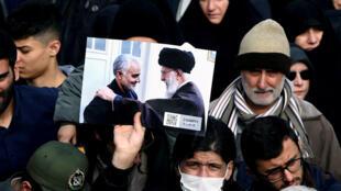 Mmoja wa waandamanaji akishikilia mikononi picha ya Ayatollah Ali Khamenei akiwa pamoja na jenerali Qassem Soleimani (kushoto) wakati wa maandamano dhidi ya shambulizi la Marekani, Baghdad, Januari 3, 2020.