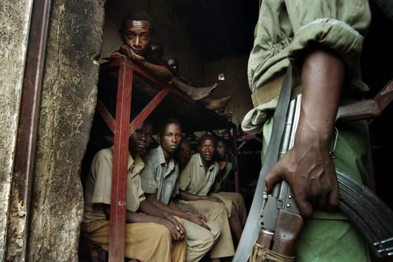 A member of the Rwandan Patriotic Front guards the entrance of a cell in a prison in Kibongo where 300 members of the former Hutu militia are being held, on 12 August, 1994.