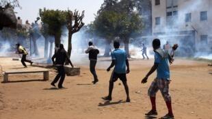 Des étudiants fuient les gaz lacrymogènes, lors d'une manifestation contyre la hausse des frais d'inscription à l'université, à Dakar, ce mardi 9 avril.