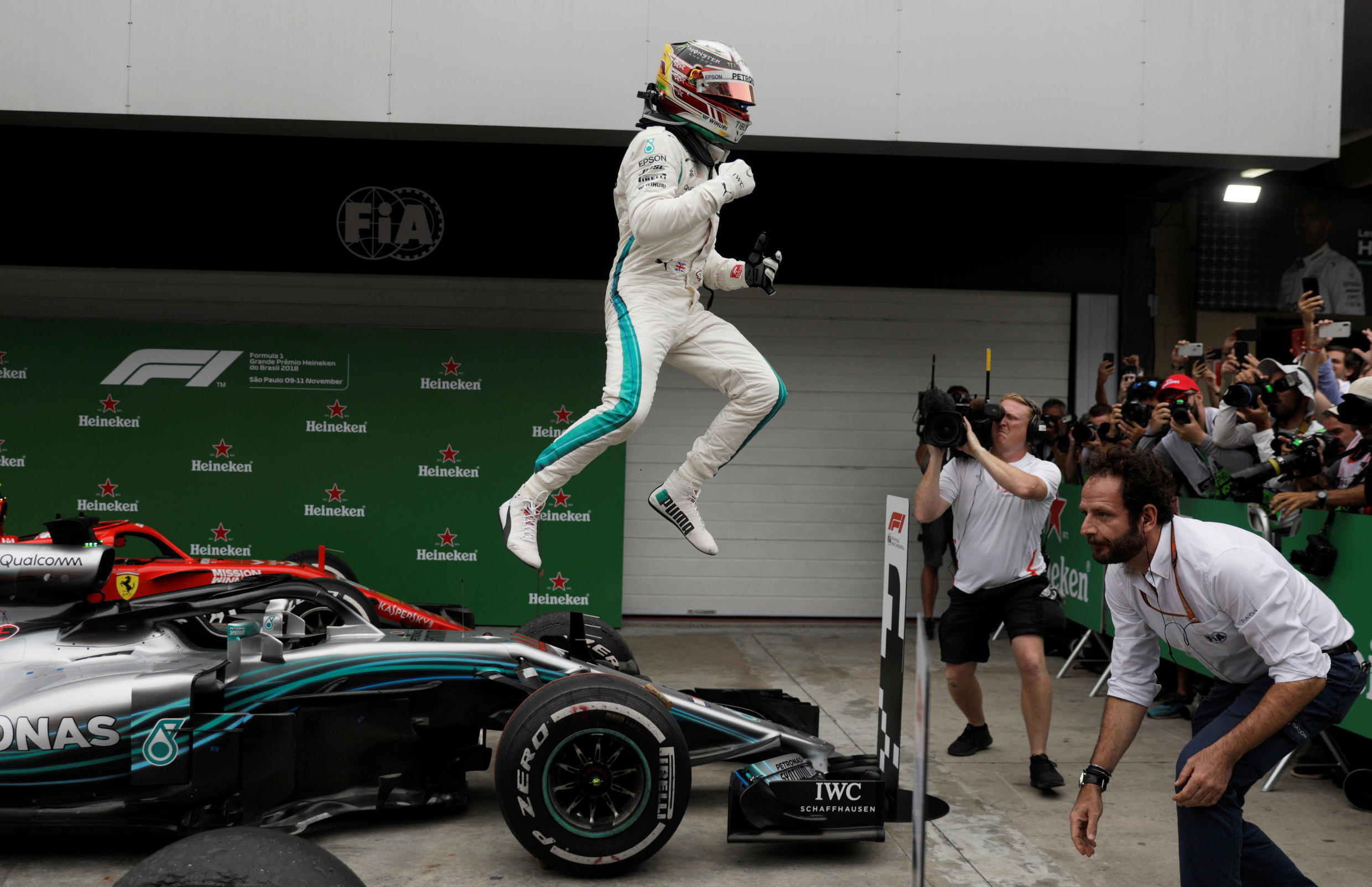 Mercedes' Lewis Hamilton celebrates with team members after winning the race.