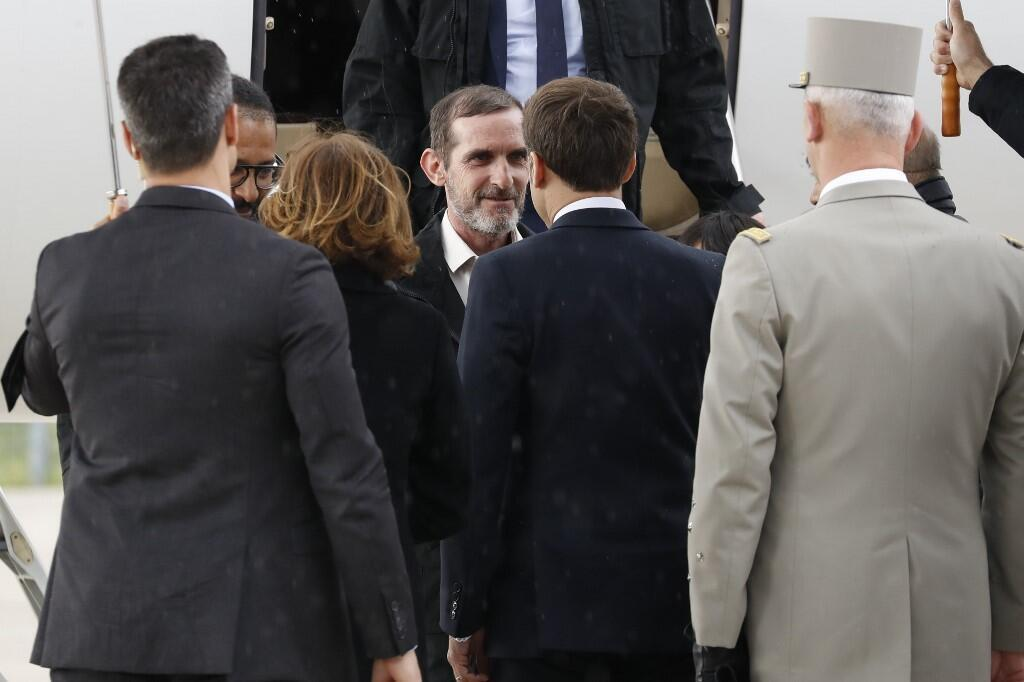 The two ex-hostages Patrick Picque (center) and Laurent Lassimouillas (l) are welcomed at Villacoublay by Emmanuell Macron (center on the back) and army chief François Lecointre (r), 11 May 2019.