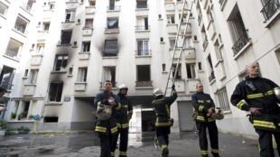 Bombeiros observam o edifício incendiado no bairro de Belleville, em Paris.