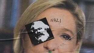 Graffiti and a picture of Karl Marx deface a Marine Le Pen poster in Paris