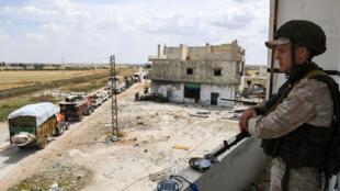 Un militaire russe surveille un convoi de camions transportant des Syriens, le 1er juin 2018.