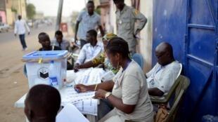 Des membres d'un bureau de vote examinent les listes dans une rue de Ndjamena, le 10 avril 2016.