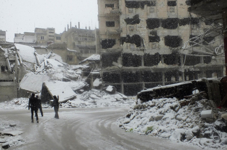 Soldados do exércio livre sírio patrulham as ruas de Homs, cobertas pela neve.