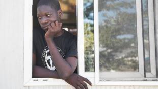 Un homme regarde par la fenêtre tandis que des personnes fuient la violence après le meurtre d'un chef de gang local campant dans la cour de la mairie de la Cité Soleil à Port-au-Prince, le 7 décembre 2019.