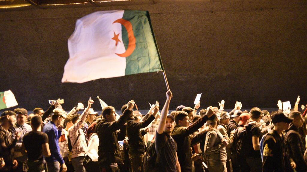 Des étudiants algériens agitent un drapeau national alors qu'ils participent à une manifestation contre le gouvernement en place à Alger, le 2 avril 2019.