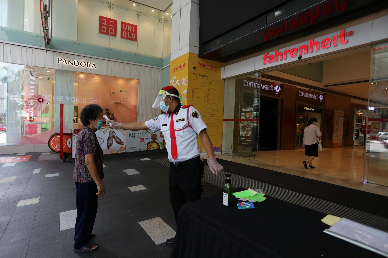 (Ảnh minh họa) - Một nhân viên an ninh đo thân nhiệt khách hàng tại lối vào một trung tâm thương mại tại Kuala Lumpur, Indonesia, ngày 04/05/2020.