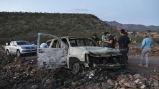 Integrantes da familia LeBarón olham um dos carros incendiados no local do massacre contra três mulheres e seis crianças mórmon no México.