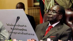 Le président du Zimbabwe, Robert Mugabe, lit une carte d'anniversaire pendant les célébrations, à Harare, de son anniversaire, le 21 février 2017.