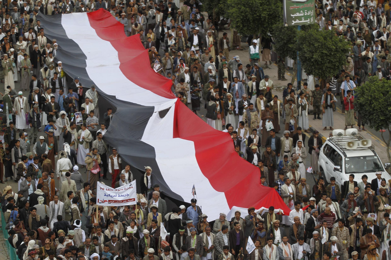 Сторонники движения хуситов с гигантским флагом Йемена во время манифестации 1 марта 2016.