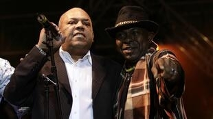 Colombian musician Joe Arroyo (L) sings with singer Wilson Saoko during a salsa concert in Mexico city