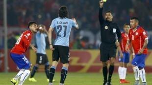 Edinson Cavani leva segundo cartão amarelo do juiz brasileiro Sandro Meira Ricci, no jogo entre Chile e Uruguai na quarta-feira (25).