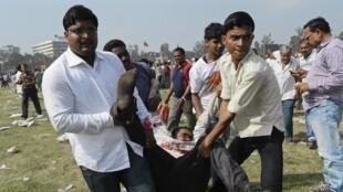 Des personnes participant à un meeting du leader politique Narendra Modi évacuent des blessés après l'explosion de plusieurs bombes, le 27 octobre à Patna (est).