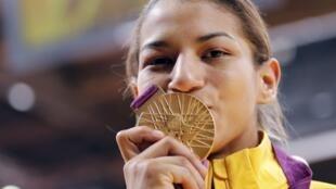 Sarah Menezes beija sua medalha de ouro inédita, a primeira do judô feminino no Brasil.