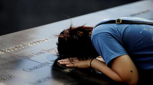 A woman lays her head on a row of names at the National September 11 Memorial, ahead of the 15th anniversary of the attacks in Manhattan, New York, September 10, 2016.