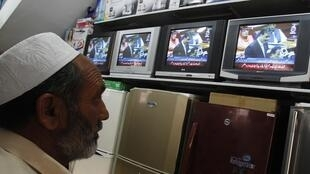 A man watches Pakistan's Prime Minister Yusuf Raza Gilani on a televised address to the parliament