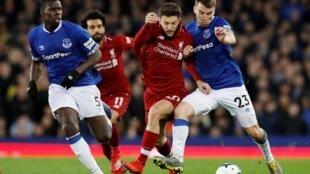 Adam Lallana de Liverpool en action avec Seamus Coleman d'Everton et Kurt Zouma, le 3 mars 2019 au Goodison Park à Liverpool.