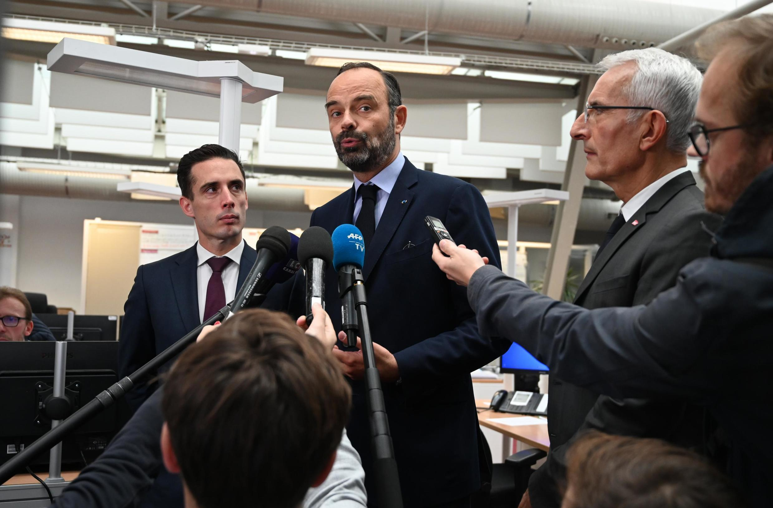 French Prime Minister Edouard Philippe (C), flanked by French Junior Minister for Transports Jean-Baptiste Djebbari (L) and CEO of France's state-owned railway company SNCF Guillaume Pepy (R) speaks at Gare de l'Est Paris' station, October 19, 2019